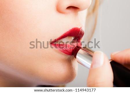 Portrait of a gorgeous woman applying lipstick