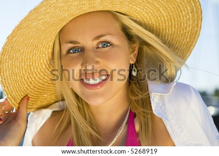 Portrait of a gorgeous young blond haired blue eyed young woman wearing a sun hat and illuminated by glorious golden evening sunshine