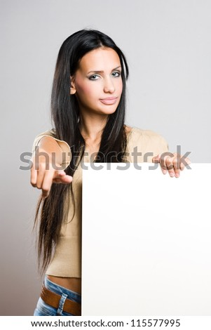Portrait of a gorgeous young brunette woman holding empty banner. - stock photo