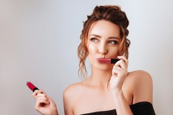 Portrait of a gorgeous young brunette woman in stylish makeup with lipsticks.