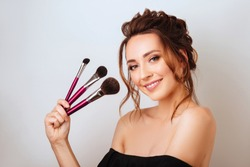 Portrait of a gorgeous young brunette woman in stylish makeup with makeup brushes.
