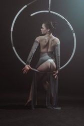 Portrait of a gorgeous young, flexible girl, of European appearance, an air acrobat, performing circus tricks on an air ring, on a black background surrounded by smoke before start of gymnastics show.