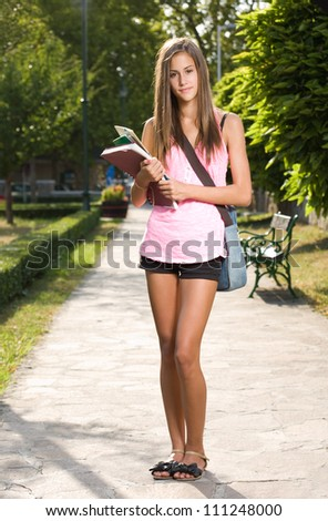 Portrait of a gorgeous young tanned student girl outdoors.