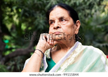 portrait of a graceful senior indian woman, senior Indian woman sitting in the lawn or garden