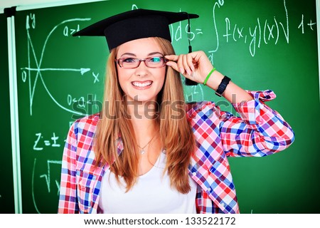 Portrait of a graduating student girl in an academic hat standing at the classroom.