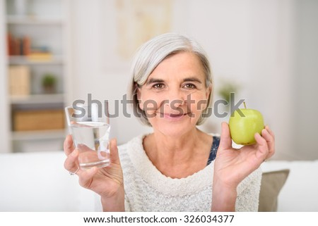 Portrait of a Gray Haired Senior Woman Holding Glass of Water and a Fresh Green Apple, Smiling at the Camera