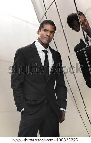 Portrait of a great looking young ethnic businessman in elegant black and white suit against shiny reflective wall