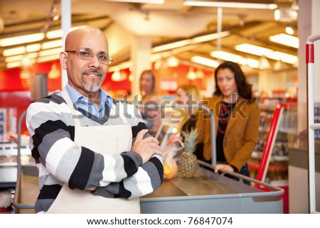 Portrait of a grocery store cashier standing at a checkout counter