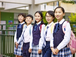 portrait of a group of asian elementary school children looking at camera smiling
