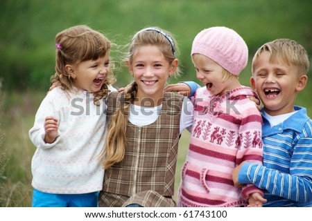 portrait of a group of children happily laughing and playing on the grass