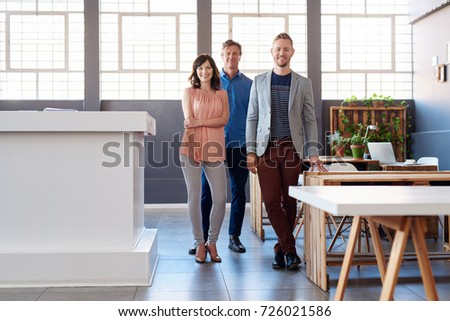 Portrait of a group of confident work colleagues smiling while standing together in a large modern office Foto stock ©