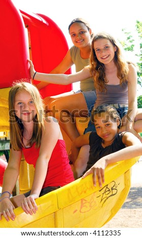 Portrait of a group of four young girls on a school playground - stock photo