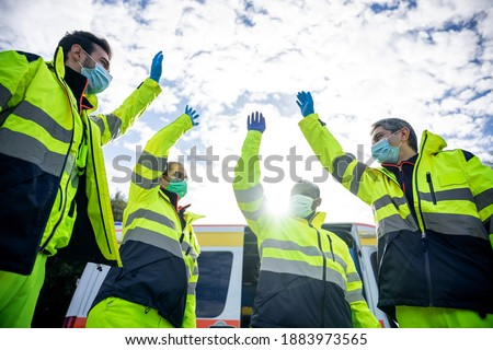 Portrait of a group of paramedics at the end of their shift in front of the ambulance while they high-fives in the air dressed in uniform and wearing a mask for protection from Coronavirus, Covid-19 Foto stock ©
