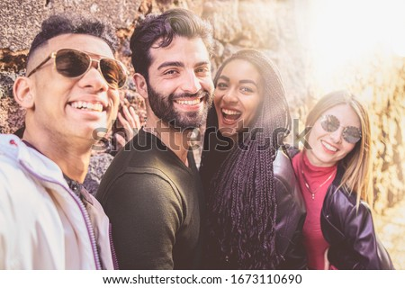 Portrait of a group of young multiracial people having fun taking a selfie with their smartphones. Millennial people outdoors taking self portraits using new technologies in a sunny day. Сток-фото ©