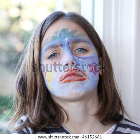 portrait of a grumpy caucasian child with her face painted