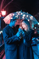 Portrait of a guy and a girl under an umbrella on a night street