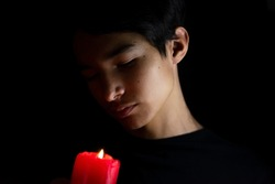 Portrait of a guy on a black background. Asian teenager. Red candle. A teenager at a funeral. The funeral. Low key portrait.  One light source. Half face in shadow. Black background. Portrait