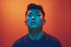 Portrait of a guy with colorful neon light on gradient studio background. Male model with calm and serious mood. Facial expression, cyberpunk, millenials lifestyle and look like. Future, technologies.