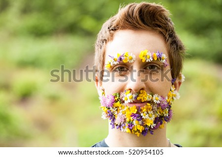 311065d188 portrait of a guy with flowers instead of his beard relaxed in the nature   520954105