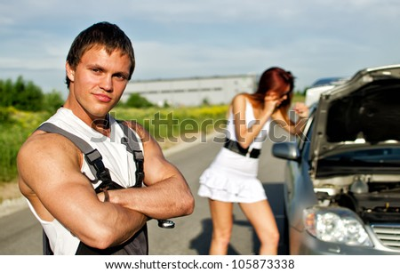 Portrait of a hadsome mechanic with a girl near broken car on a background