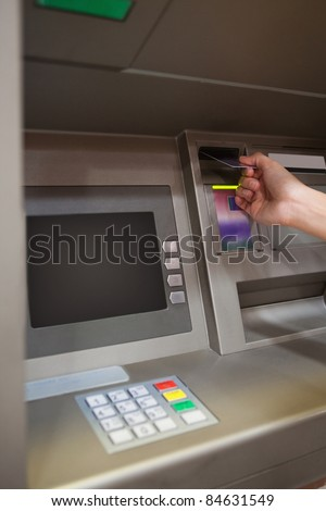 Portrait of a hand inserting a credit card in an ATM