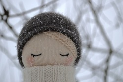 Portrait of a handmade soft toy of a girl in a knitted gray hat with snowflakes on the villi