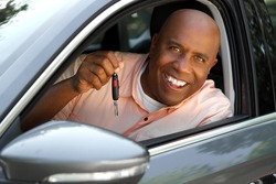 Portrait of a handsome African American man driving his car.