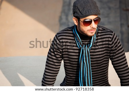 portrait of a handsome and confident man wearing sweater and cap in outdoor, handsome man wearing sunglasses