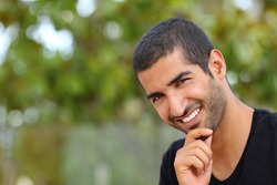 Portrait of a handsome arab man face outdoors in a park with a green background