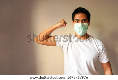Portrait of a handsome Asian man wearing medical protective mask standing with a raised arm shows strong biceps. Isolated background. Concept of staying strong and healthy against coronavirus covid-19
