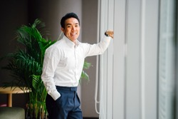 Portrait of a handsome, athletic young Chinese Asian man in his office during the day. He is standing by the window his office and is wearing a well cut professional shirt and pants.