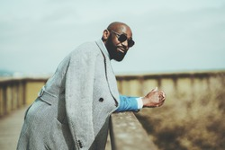 Portrait of a handsome bearded bald African man in sunglasses and coat leaning on a wooden fence outdoors, selective focus, shallow depth of field, a copy space place on the right for an ad message