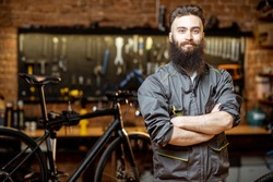 Portrait of a handsome bearded repairman in workwear at the bicycle workshop