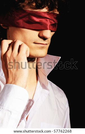 Portrait of a handsome blindfold man on black background