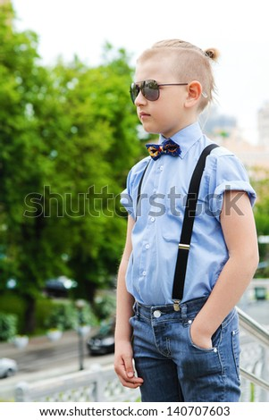 Portrait of a handsome boy with a creative hairstyle on background of the city. A boy with a fashionable hairstyle in blue shirt. Boy in sun goggles. Sunglasses have a little boy.