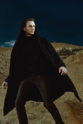 Portrait of a handsome brunet man model walking in a desert in black clothes. Sands and clear blue skies. Men's fashion.