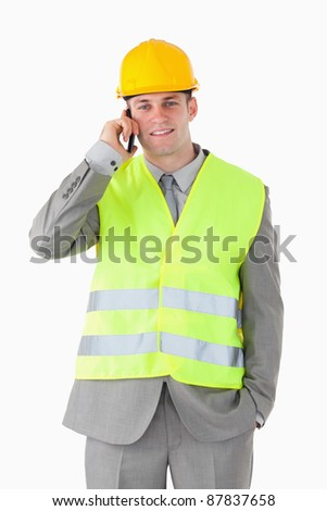 Portrait of a handsome builder making a phone call against a white background