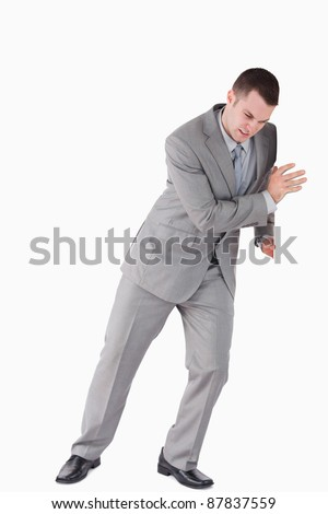 Portrait of a handsome businessman pushing a wall against a white background