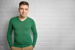Portrait of a handsome caucasian man smiling. Brick wall background. Studio photo. There is a place to copy space.