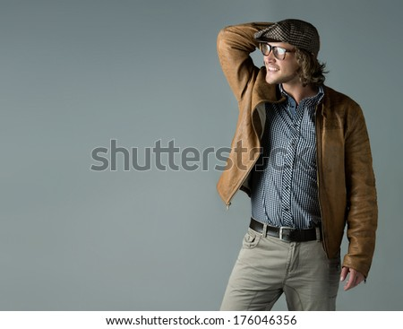 Portrait of a handsome caucasian man wearing a leather jacket blue checkered button shirt beret and retro glasses.