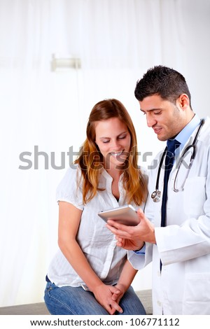 Portrait of a handsome doctor and a female patient looking something on tablet PC at hospital - stock photo