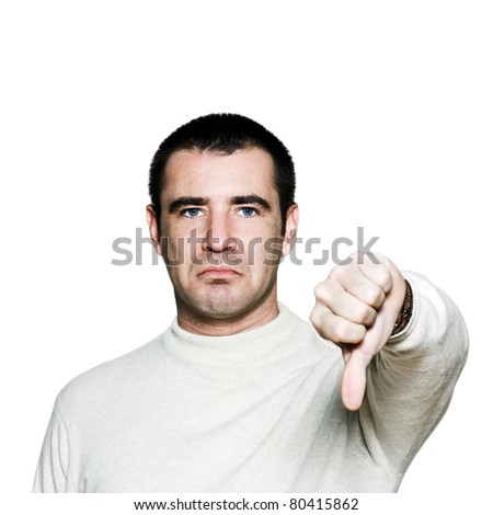 Portrait of a handsome expressive man showing thumbs down sign in studio on white isolated background