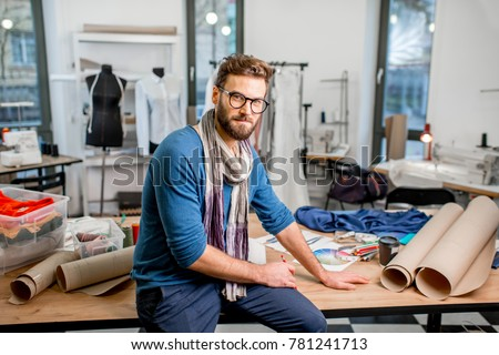 Portrait of a handsome fashion designer sitting with paper sketches at the studio full of tailoring tools and clothes #781241713