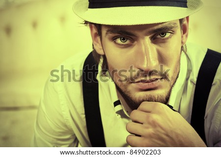 Portrait of a handsome fashionable man posing in the interior.