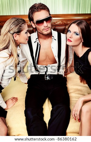 Portrait of a handsome fashionable man with two charming women posing in the interior.