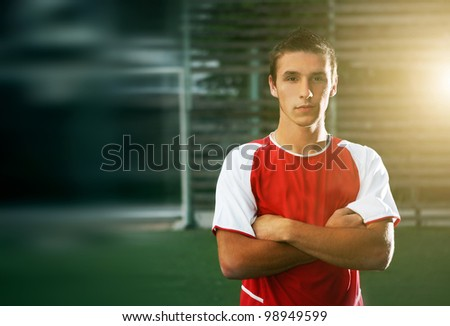 portrait of a handsome football player with his arms crossed in training