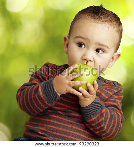 portrait of a handsome kid biting a green apple at a park