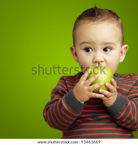 portrait of a handsome kid bitting a green apple over green background