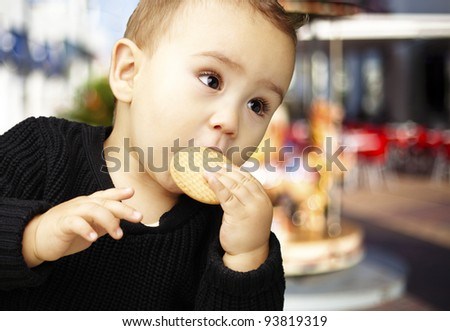portrait of a handsome kid eating a biscuit against a carousel