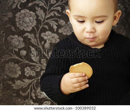 portrait of a handsome kid eating a biscuit against a vintage wall